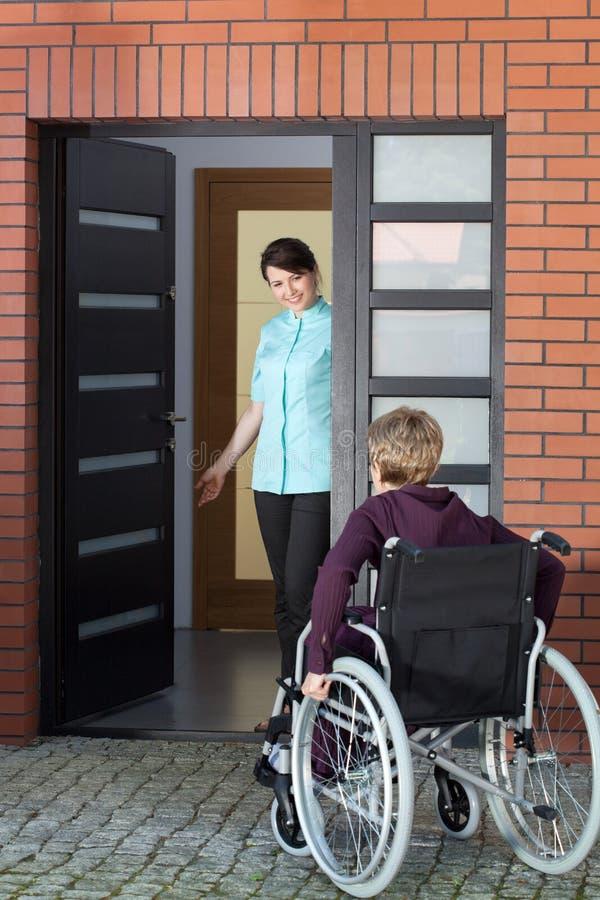 Einladende Frau der Pflegekraft auf Rollstuhl zum Pflegeheim stockfotografie