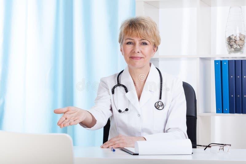 Einladender Patient Doktors auf einem Stuhl stockbild