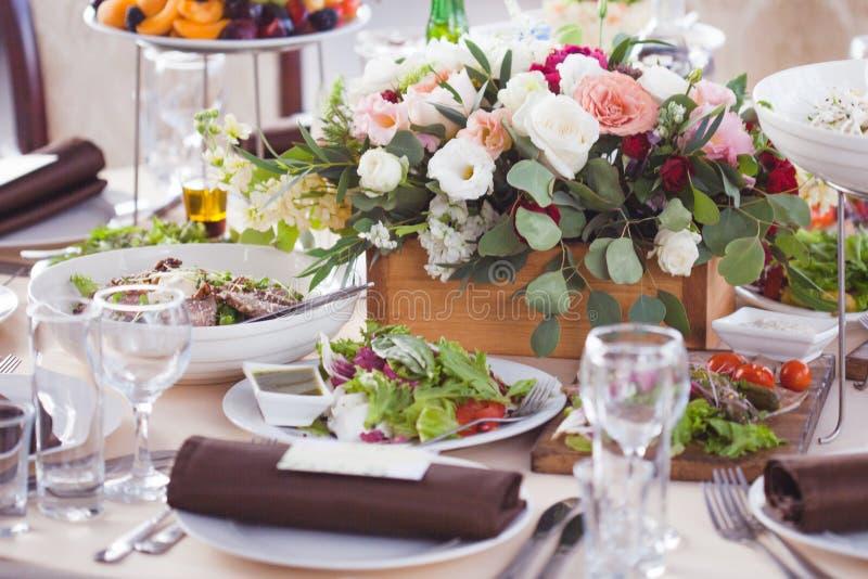 Einladungskarte mit Perlendekoration und Rosen Boutonniere auf weißem Hintergrund Blumen im Restaurant, Lebensmittel auf dem Tisc stockfotos