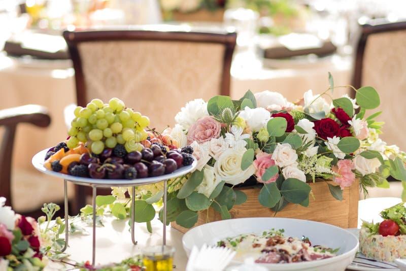 Einladungskarte mit Perlendekoration und Rosen Boutonniere auf weißem Hintergrund Blumen im Restaurant, Lebensmittel auf dem Tisc lizenzfreie stockfotos