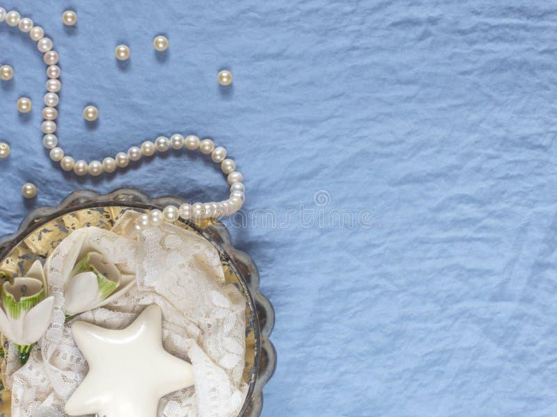 Einladungskarte mit Perlendekoration und Rosen Boutonniere auf weißem Hintergrund Weiße keramische Blumen, Perlen, keramischer we lizenzfreies stockbild