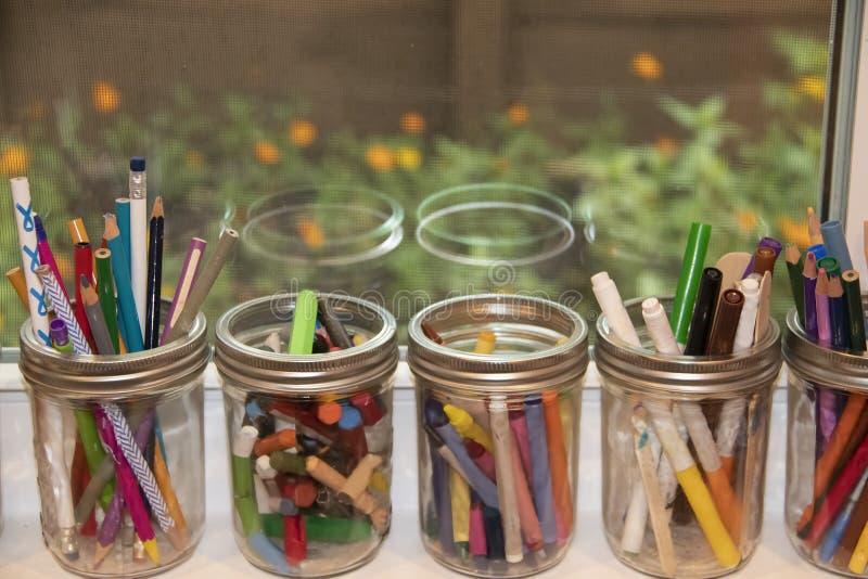 Einmachende Gläser füllten mit den Zeichenstiften, Pastellen und Markierungen, die auf einem offenen Fensterbrett mit der Blumena stockfoto