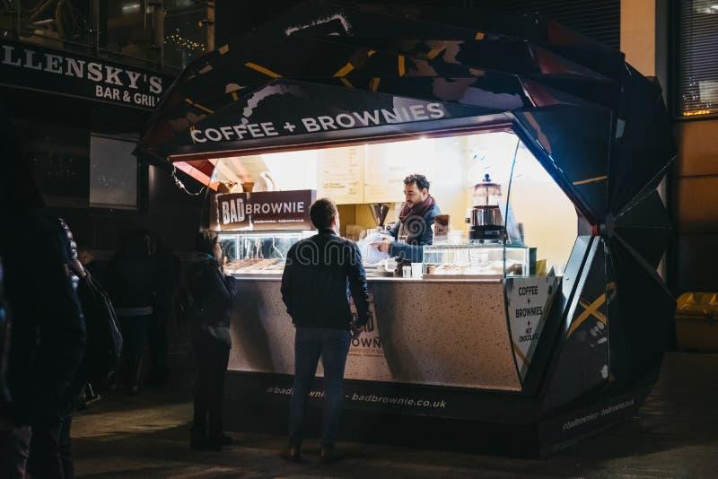 Einrichtungsgetränke der Leute von einem Kaffee und von den Schokoladenkuchen klemmen in Canary Wharf, London, Großbritannien fes stockfotografie