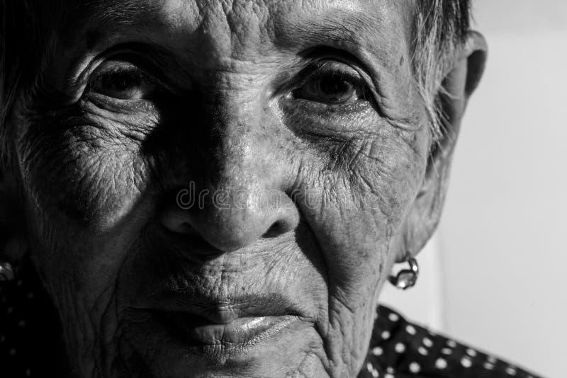 Einsame ältere Frau, die in camera lächelt lizenzfreies stockfoto