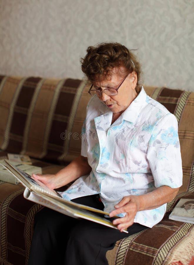 Einsame ältere Frau schaut ein Familienabbildungalbum lizenzfreie stockbilder
