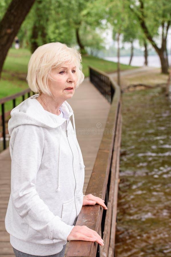 einsame ältere Frauenstellung nahe Geländern lizenzfreie stockfotografie