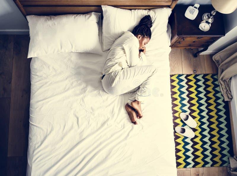 Einsame Afroamerikanerfrau auf Bett allein schlafend stockfotografie