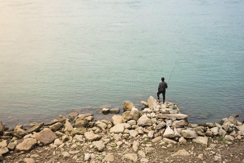 Einsame asiatische Fischerstellung auf Felsen vor Wasser lizenzfreie stockbilder