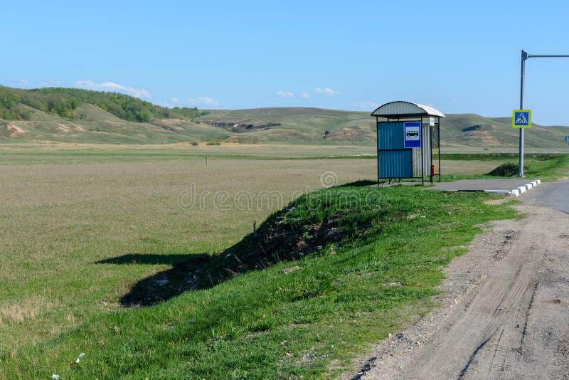 Einsame Bushaltestelle auf dem Hintergrund einer schönen Frühlingslandschaft, -felder, -wiesen, -wälder und -hügel Busverbindung  lizenzfreies stockbild