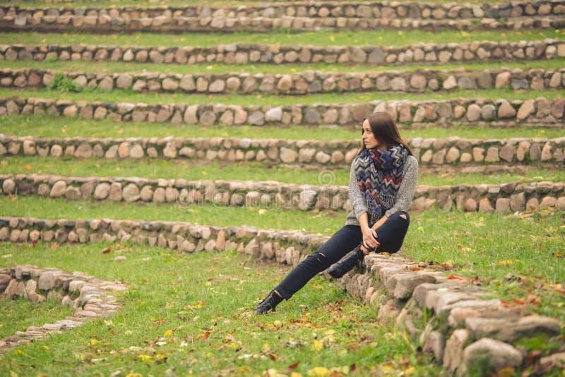 Einsame Frau, die allein auf den Steinen in den Herbstgarten sitzt stockbilder