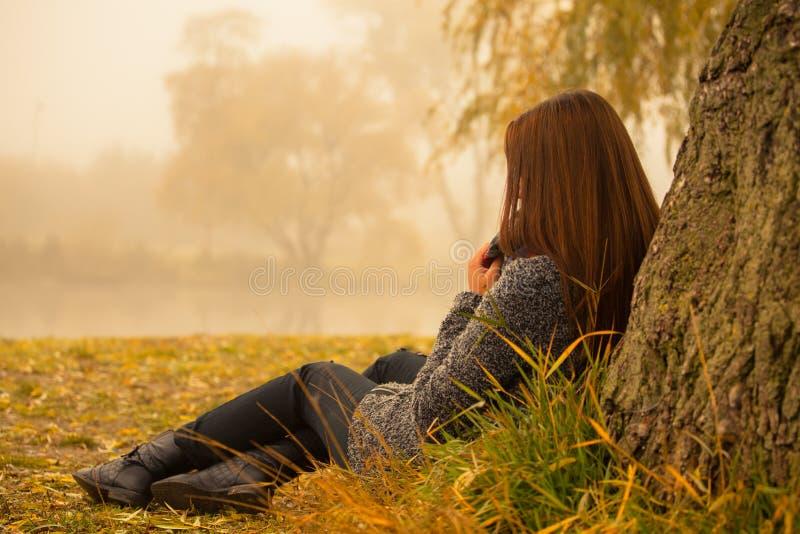 Einsame Frau, die Rest unter dem Baum nahe dem Wasser in einem nebeligen Herbsttag hat stockbilder