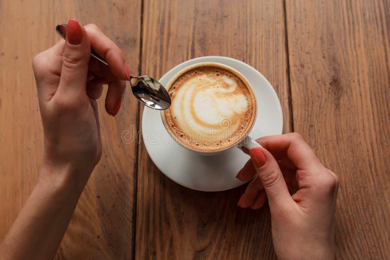 Einsame Frau mit netter Maniküre in trinkendem Kaffee der warmen hölzernen Strickjacke morgens, Draufsicht von den weiblichen Hän stockbilder