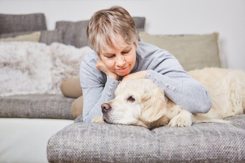 Einsame Frau streichelt mit Hund lizenzfreie stockbilder