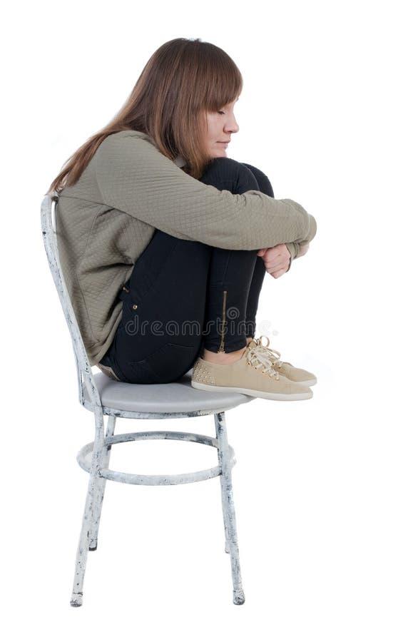 Einsame, geschlossene Frau, die auf Stuhl sitzt stockbild
