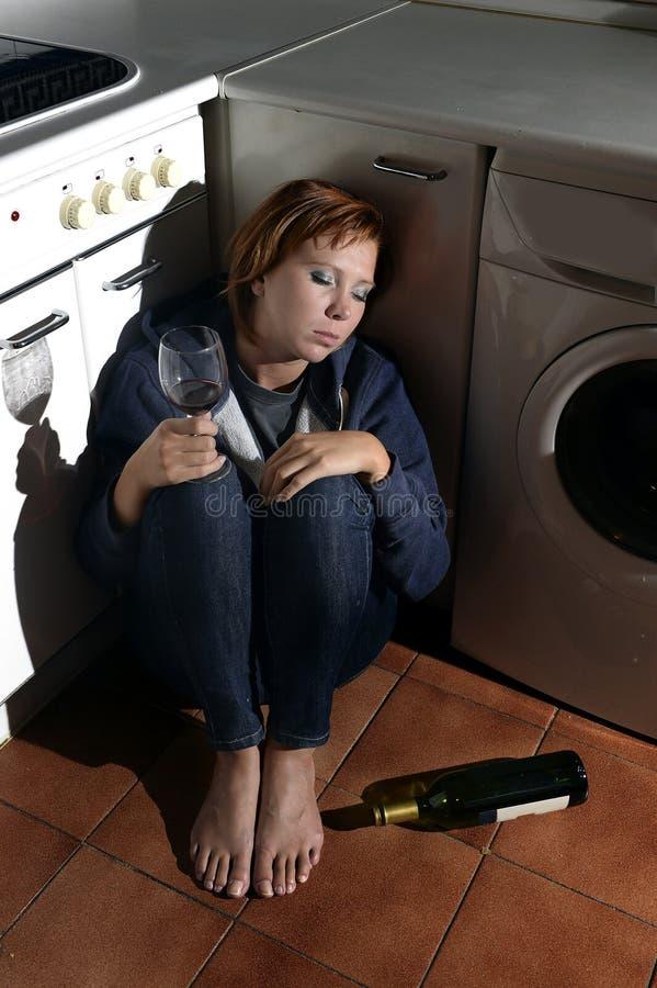 Einsame getrunkene alkoholische Frau, die auf Küchenboden in trinkendem Wein der Krise sitzt lizenzfreie stockfotografie