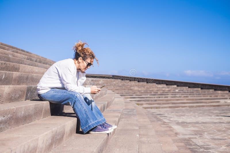 Einsame Mittelalterfrau bei der Arbeit mit einem Smartphone, der auf lange schöne staris in der städtischen Wettbewerbfreizeit mi lizenzfreies stockfoto
