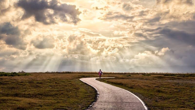Einsame Person geht entlang einen Weg in die Sonnenstrahlen stockfotos