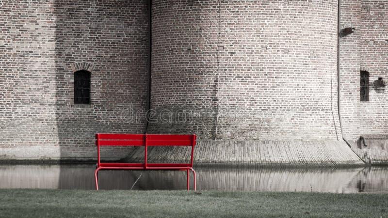 Einsame rote Holzbank gegen eine Backsteinmauer des alten Schlossgebäudes und -burggrabens lizenzfreie stockfotografie