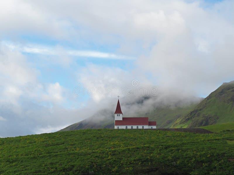 Einsame rote weiße Kirche im vik in den Hügeln grünen Grases Islands stockfotos
