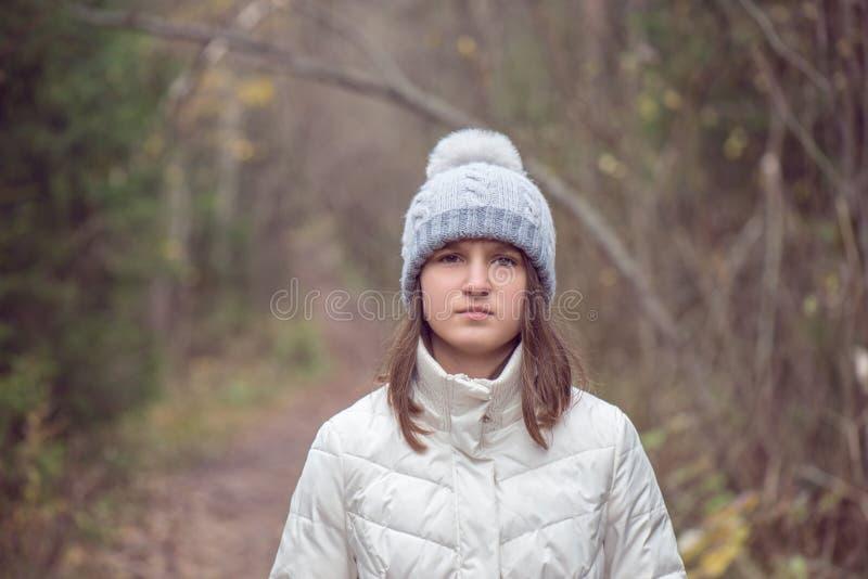Einsame Stellung des jugendlich Mädchens im Wald oder Park, traurig stockbild