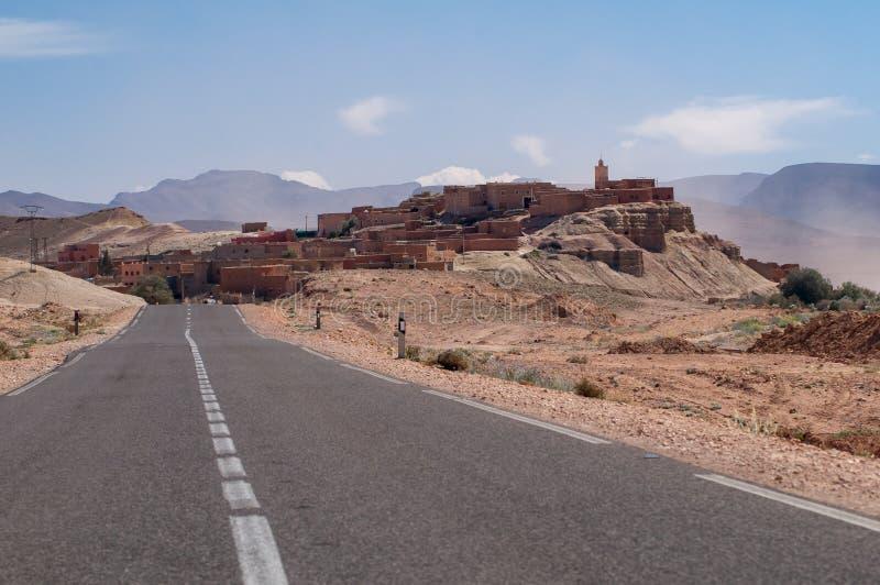 Einsame Straße zu einem kleinen Dorf in der Wüste von Marokko stockfoto