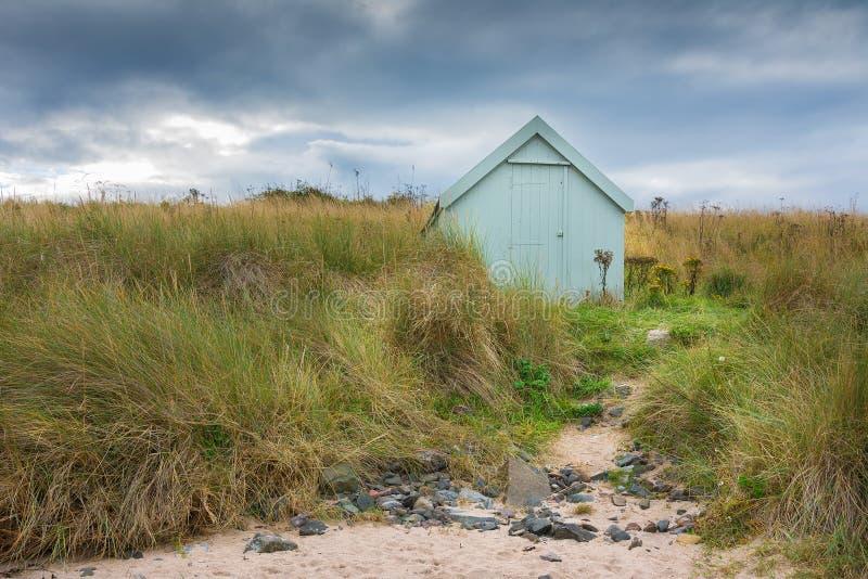 Einsame Strandhütte unter stürmischem Himmel in den Sanddünen stockbilder