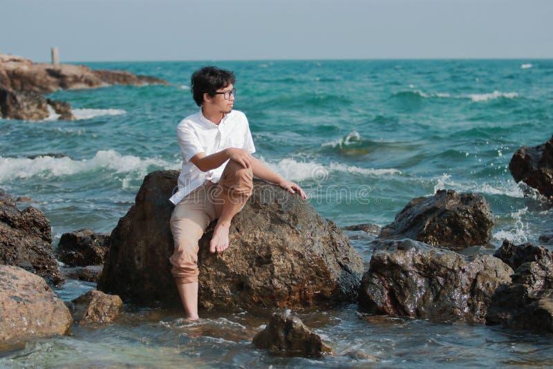 Einsamer hübscher junger asiatischer Mann, der auf dem Felsen an der Küste sitzt stockfoto