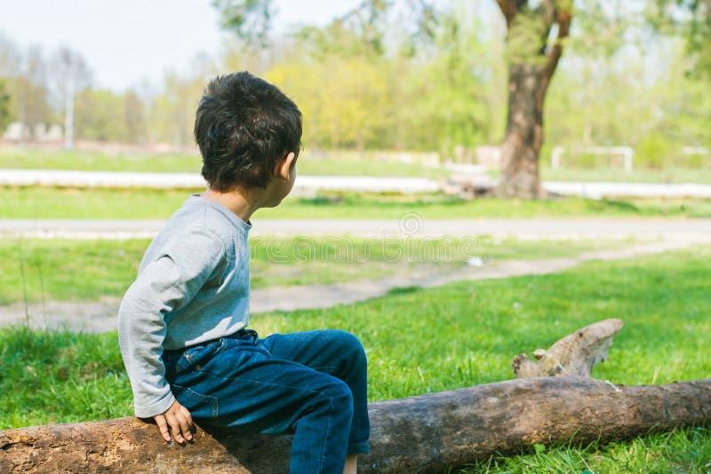 Einsamer Junge, der auf einem Klotz sitzt lizenzfreie stockfotografie