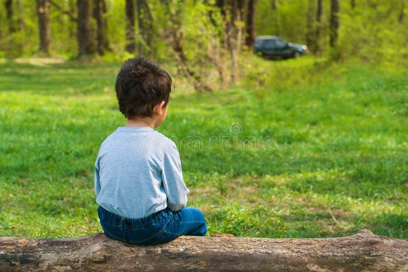 Einsamer Junge, der auf einem Klotz sitzt stockfoto