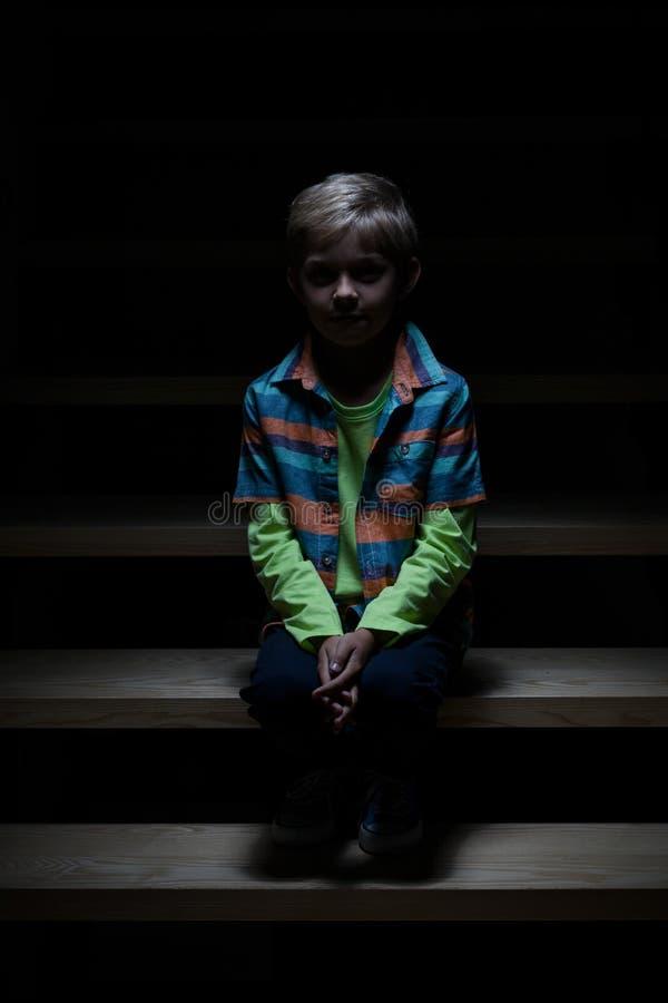 Einsamer Junge, der auf Treppenhaus sitzt lizenzfreie stockbilder