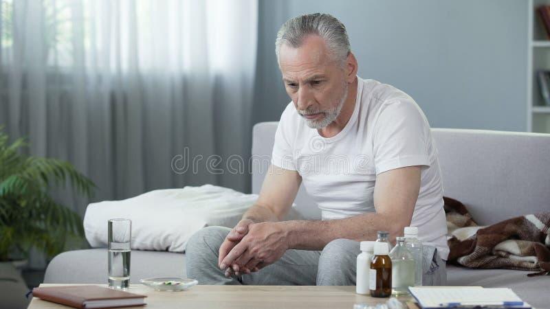 Einsamer kranker älterer Mann, der auf Couch sitzt und an das Leben, Krise denkt stockfotografie