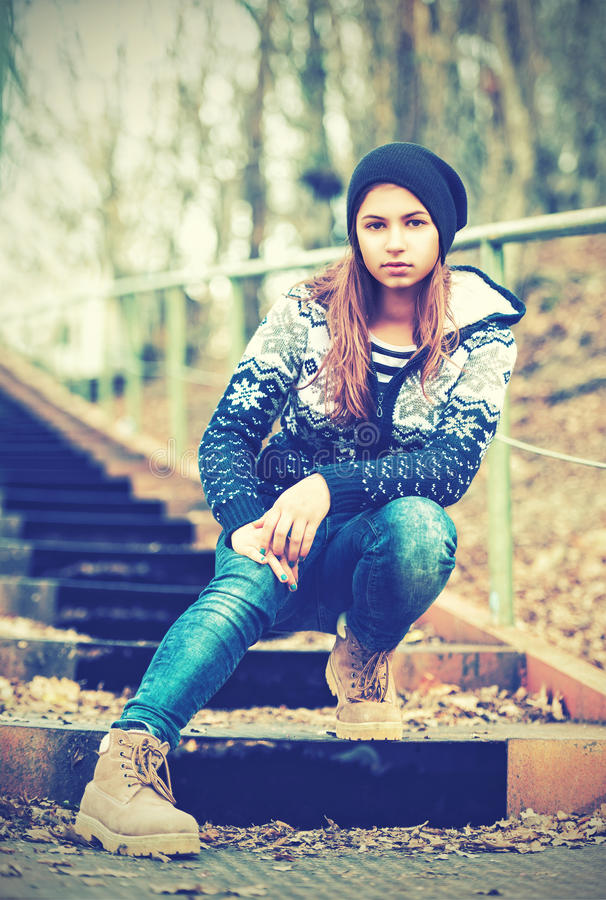Einsamer Mädchenjugendlicher im Hut, der auf Treppe und traurigem Herbst sitzt lizenzfreie stockfotografie