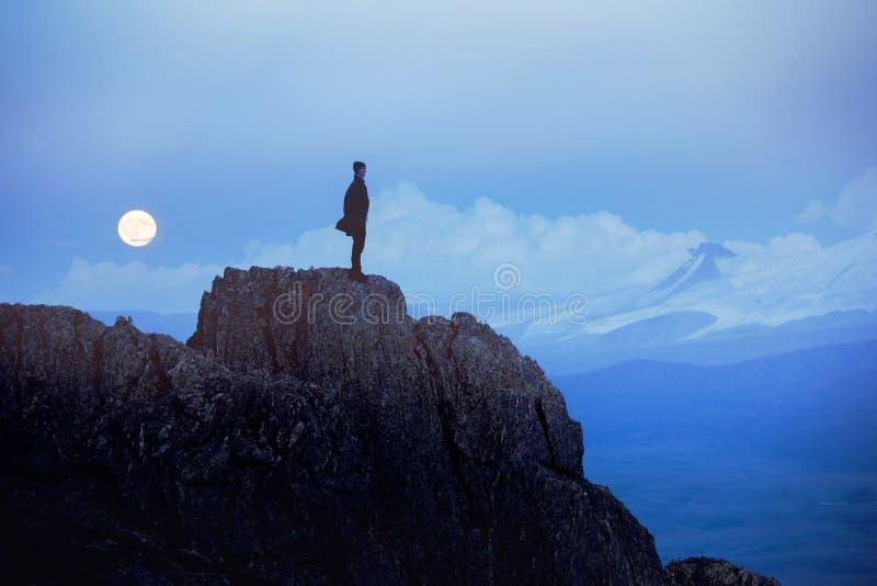 Einsamer Mann am Abend steht auf Klippe gegen Berge und Mond stockfotografie