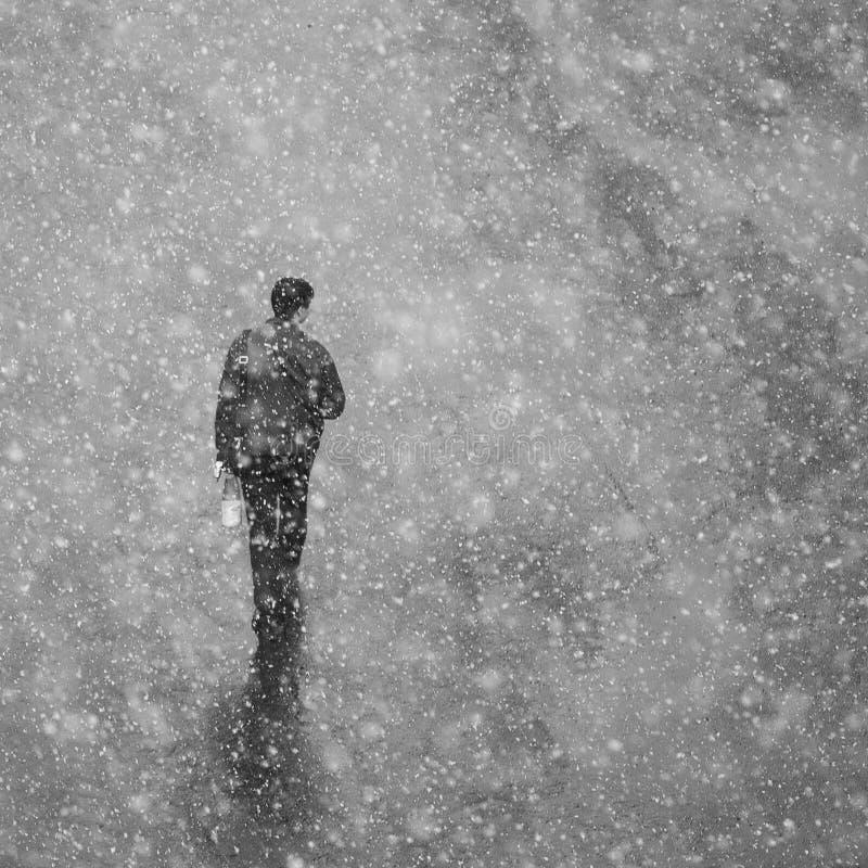 Einsamer Mann, der auf die Straße im Schnee geht Ein Mann in einer Jacke geht lizenzfreie stockfotografie