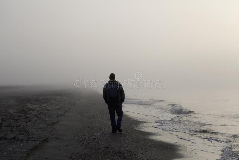 Einsamer Mann, der auf einen Strand geht stockbild