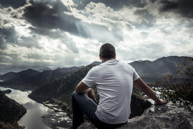 Einsamer Mann, der mit Hoffnung auf Horizont auf Bergspitze mit drastischem Sonnenlicht während des Sonnenuntergangs mit Effekt d stockbild