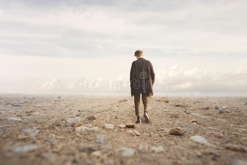 Einsamer Mann geht in Richtung zu einem unbekannten Bestimmungsort in einer Wüste stockfoto