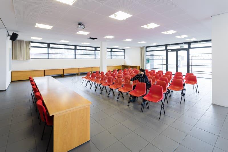Einsamer Mann im leeren Konferenzsaal, Konzept lizenzfreie stockfotografie