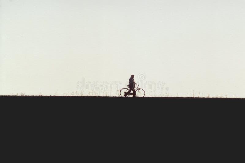 Einsamer Mann mit einem Fahrrad lizenzfreie stockbilder