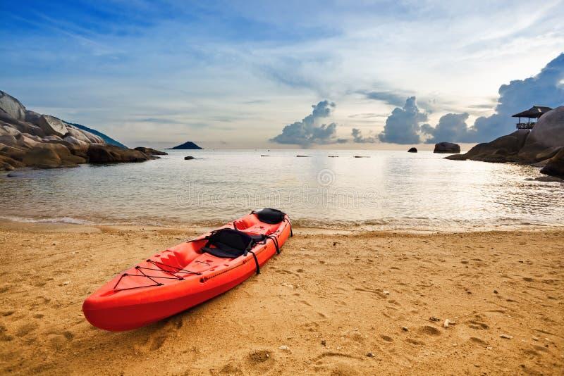 Einsamer roter Kajak am tropischen Strand lizenzfreie stockbilder