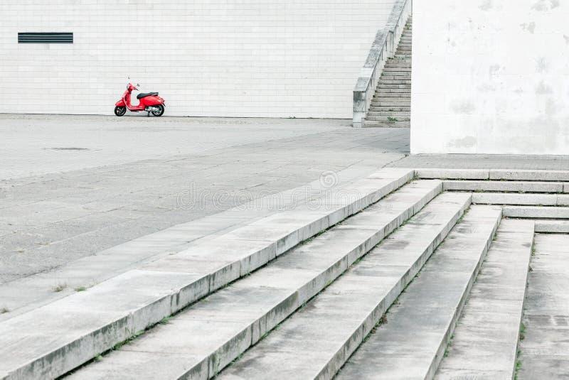 Einsamer roter Roller gegen weiße Wand in der städtischen Umwelt stockfotos