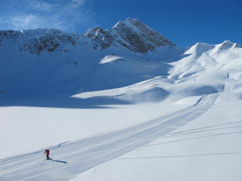 Einsamer Skifahrer auf Ski piste am sonnigen Wintertag lizenzfreie stockbilder