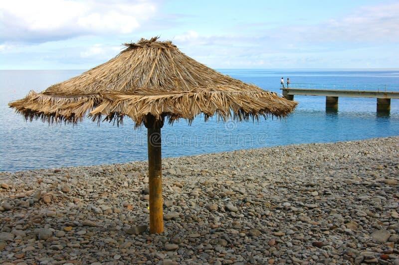 Einsamer Sonnenschutz am wilden Strand und an zwei Schattenbildern weit weg stockfotografie