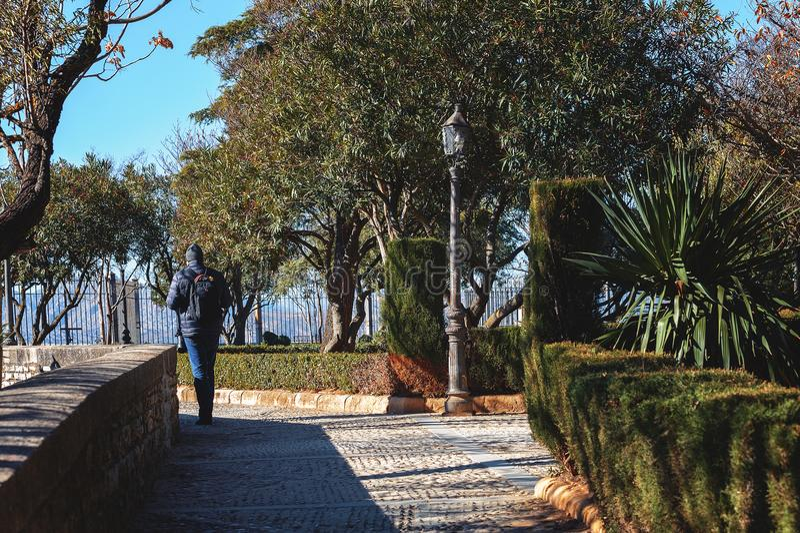 Einsamer Tourist geht weg von kleinem Park von Ronda-Stadt, Spanien lizenzfreie stockfotos