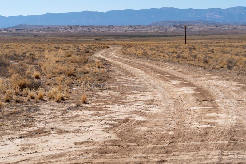 Einsamer Wüstenschmutz und -Schotterstraße im ländlichen New Mexiko stockfotografie