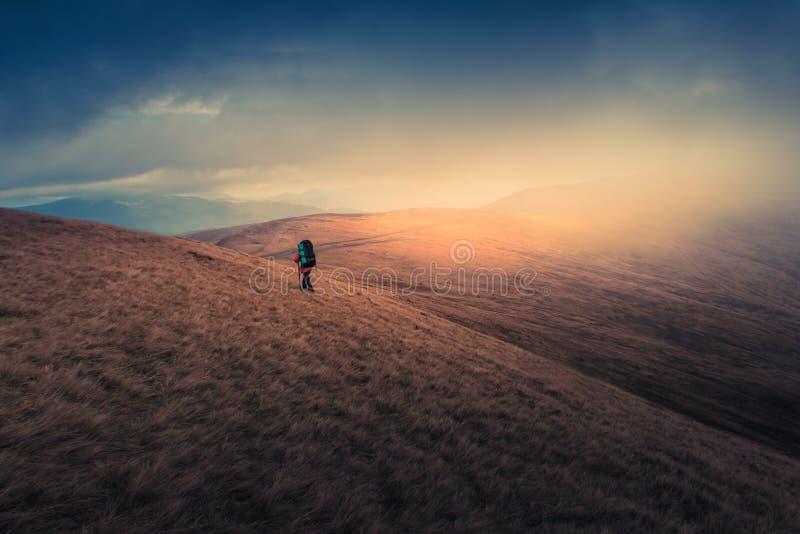 Einsamer Wanderer mit Rucksack gehend entlang die Spur auf die Gebirgsoberseite zur nebeligen Tageszeit stockbild