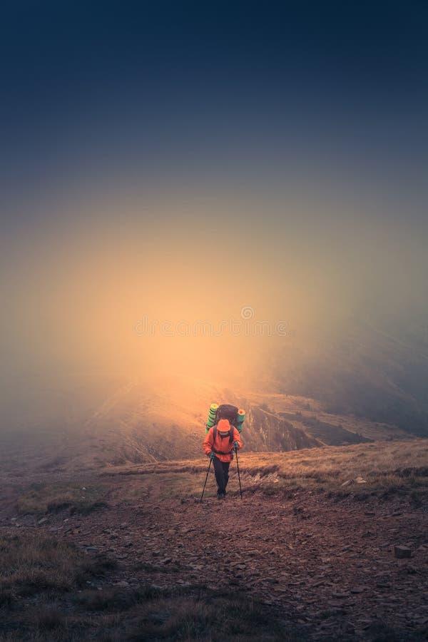 Einsamer Wanderer mit Rucksack gehend entlang die Spur auf die Gebirgsoberseite zur nebeligen Tageszeit lizenzfreie stockbilder