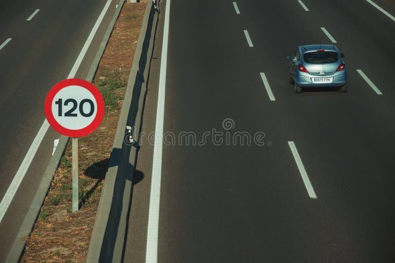 Einsames blaues Auto auf Landstraße und HÖCHSTGESCHWINDIGKEITSwegweiser in Madrid stockfotos