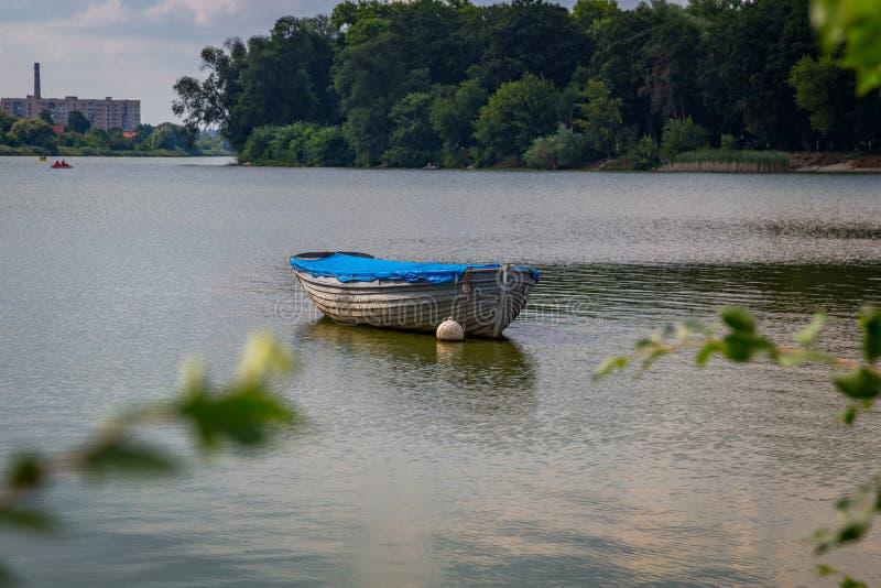 Einsames Boot auf dem Fluss an einem sonnigen Tag lizenzfreie stockfotos
