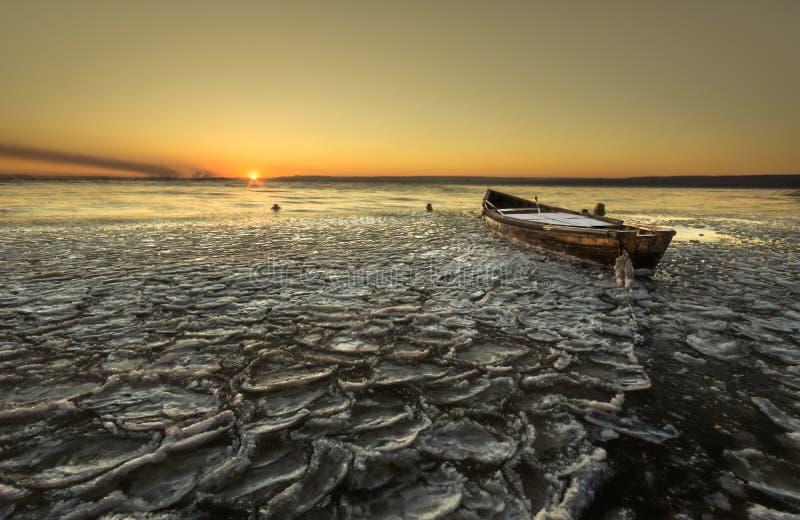 Einsames Boot auf gefrorenem Fluss stockbilder